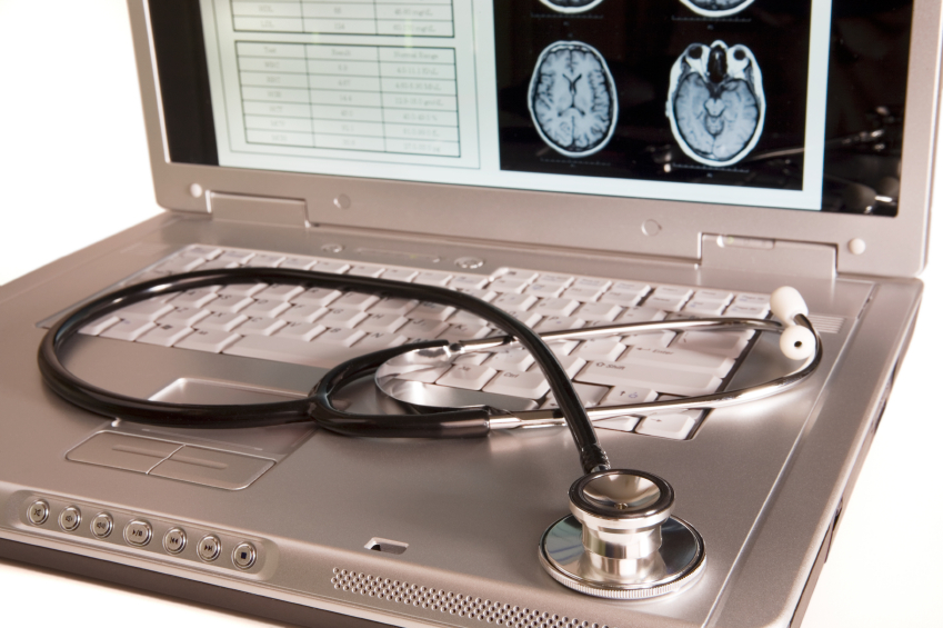 Stethoscope resting on keyboard of laptop displaying brain MRI & other medical data.  Focus is on the stethoscope head.