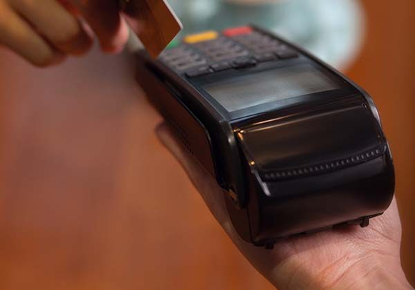 Mobile payment. Bank terminal hold by female hand and female hand with a credit or debit card to make payments